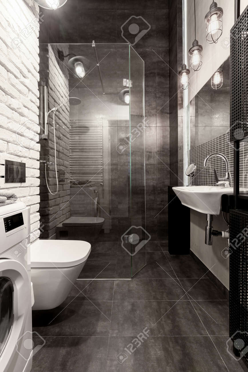 Elegant bathroom with shower behind glass wall, white brick and dark gray tiles - 159914271