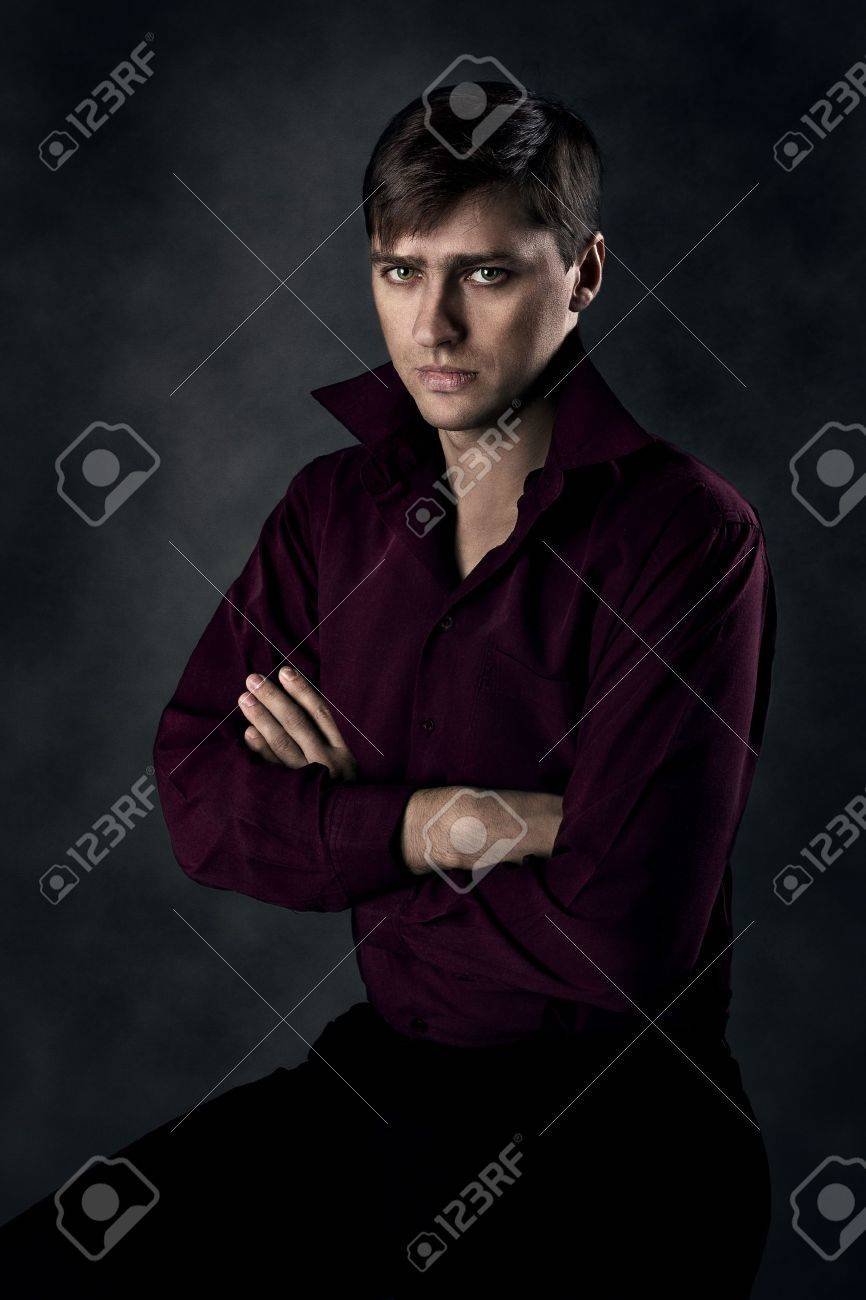 Handsome man sitting over grey background with crossed hands. Seriously looking at camera. Stock Photo - 10522777