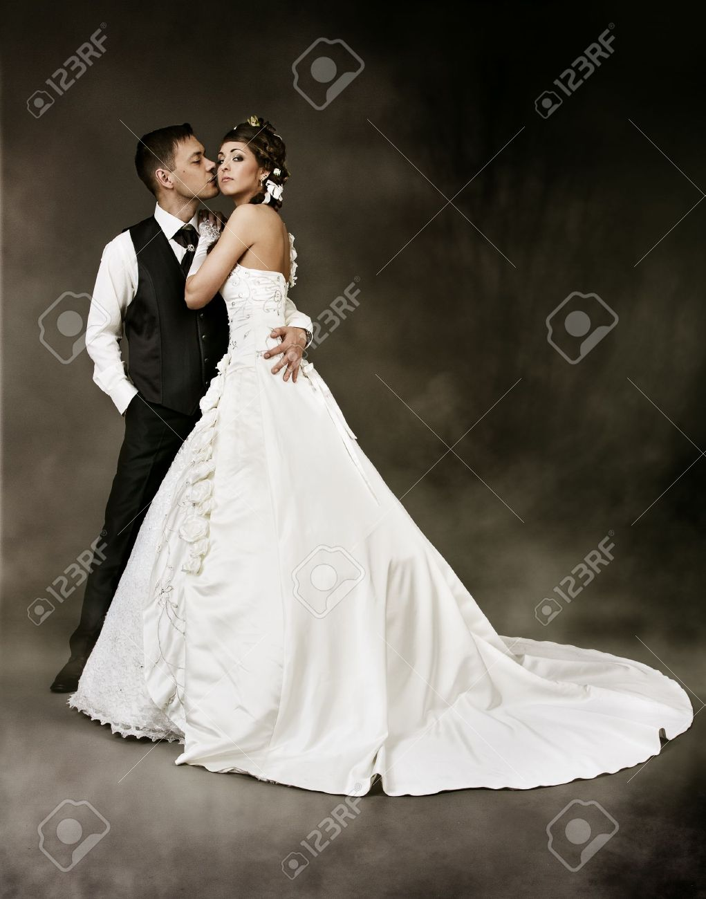 Bride and groom at dark mysterious background. Wedding couple fashion shoot. Stock Photo - 10922551