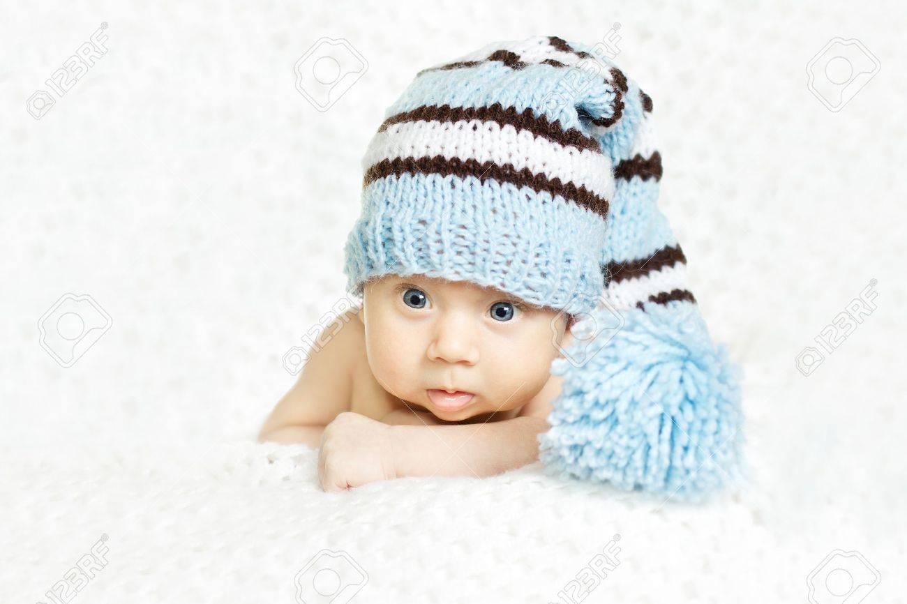 Newborn baby closeup portrait in blue woolen hat over white soft background. Indigo eyes Stock Photo - 12615606