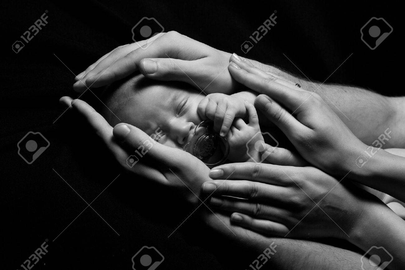 Newborn baby sleeping into parents hands  Concept  kids protection by parents  Closeup  Monochrome Stock Photo - 13841657