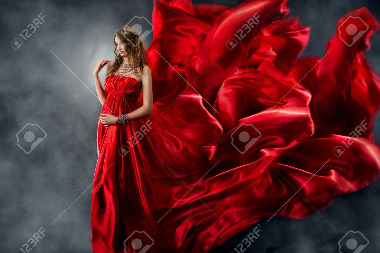 Beautiful woman in red waving silk dress as a flame. Looking down. Stock Photo - 15398434