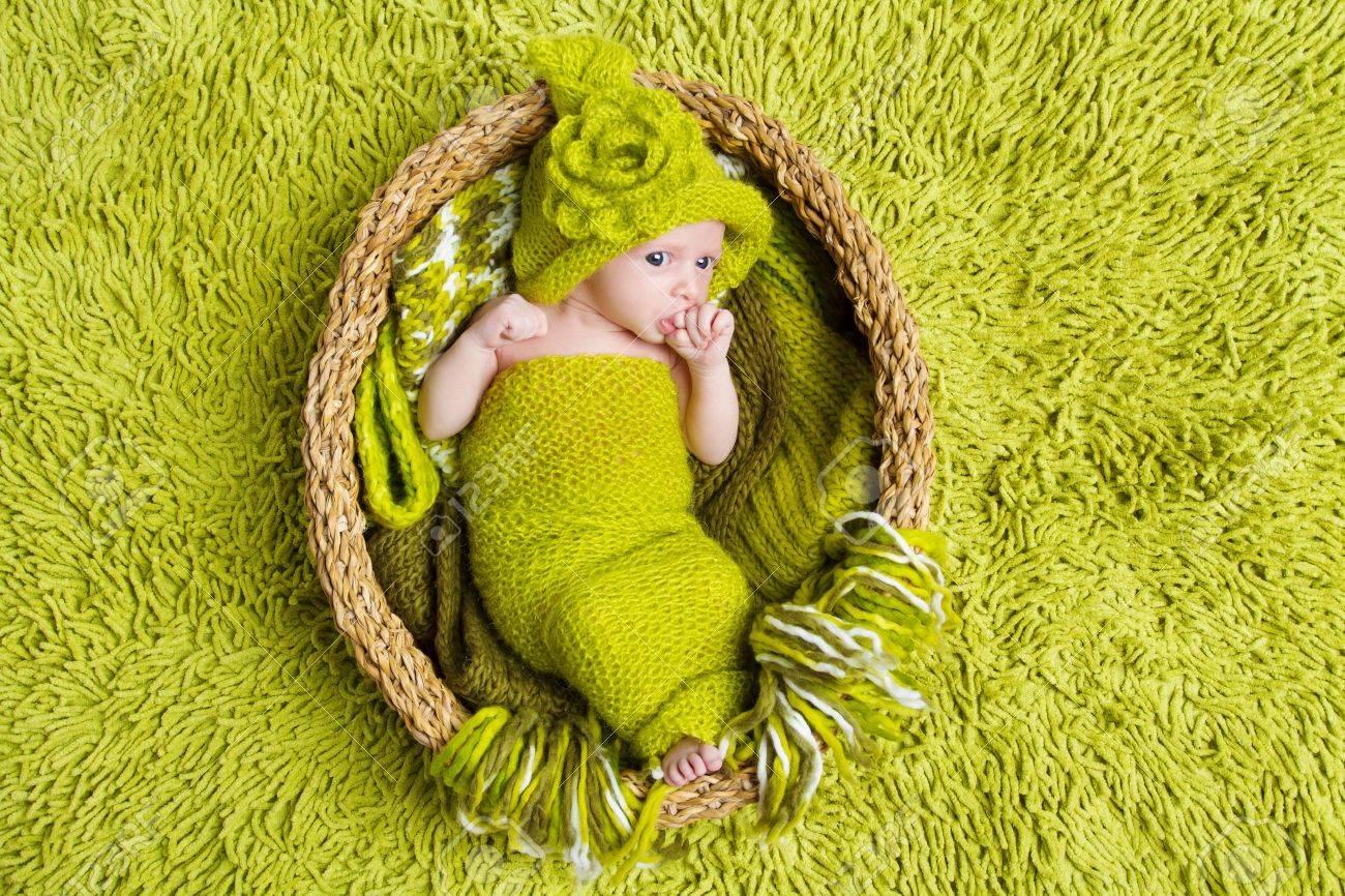1610c5a05 Newborn Baby In Woolen Hat Inside Basket Over Green Background Stock ...