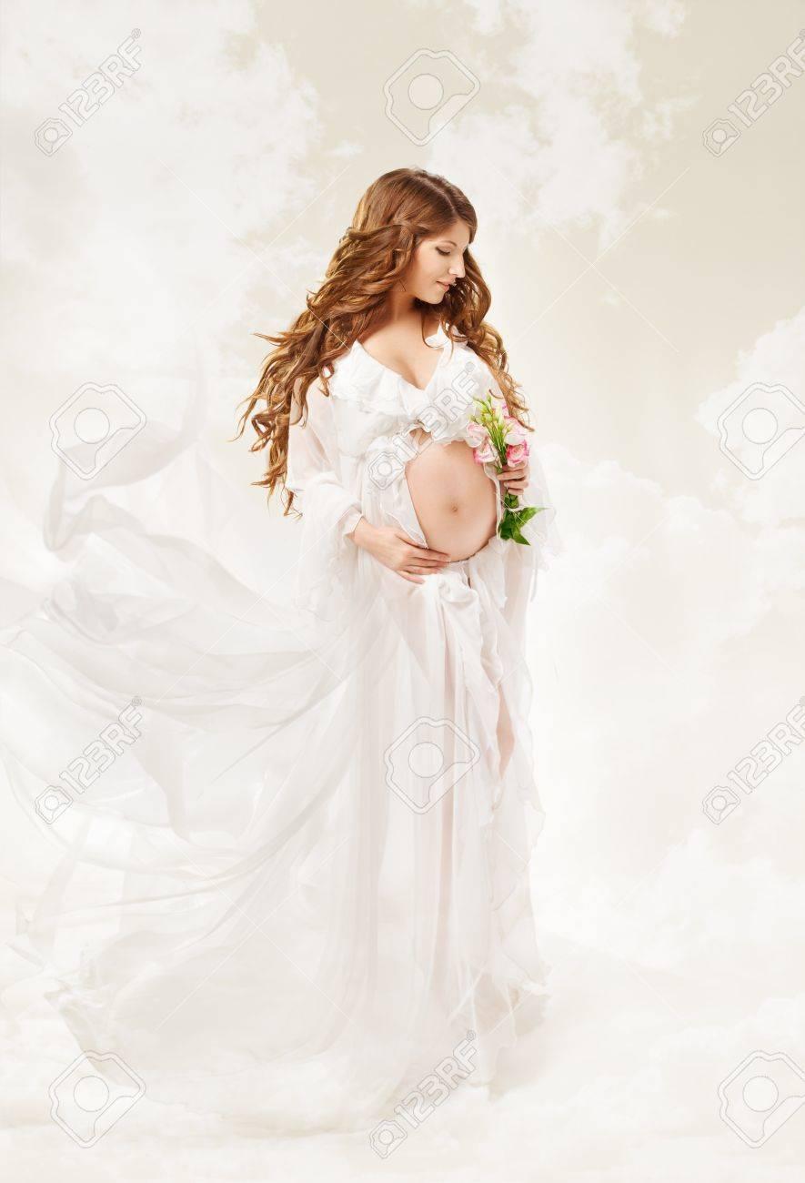 schwangere frau. schöne schwangerschaft: lange lockige haare und  chiffon-kleid auf wind flattert.
