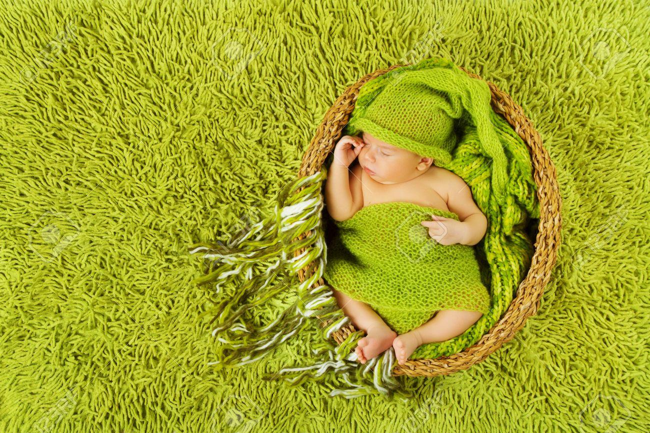 9ac8a1ba1 Baby Newborn Sleeping In Woolen Hat Inside Basket Over Green.. Stock ...