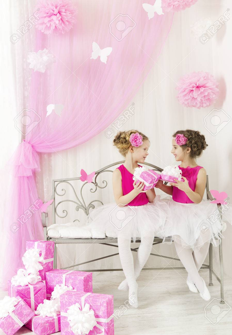 Girl Giving Children Birthday Present To Sister Kids And Party Gift Boxes In Pink Color