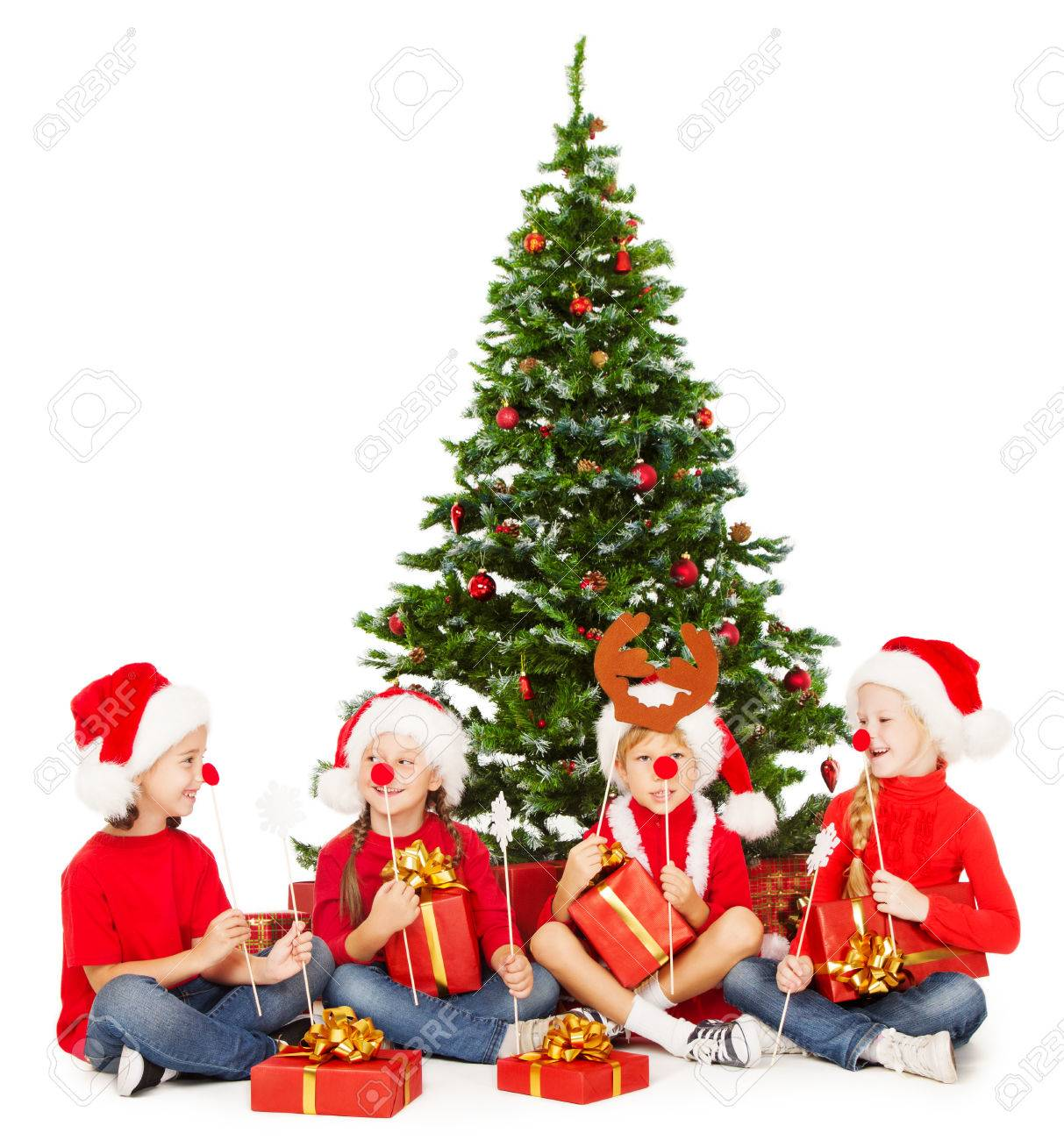 Christmas Kids In Santa Hat Playing Under Fir Tree New Year Presents And Accessories Stock