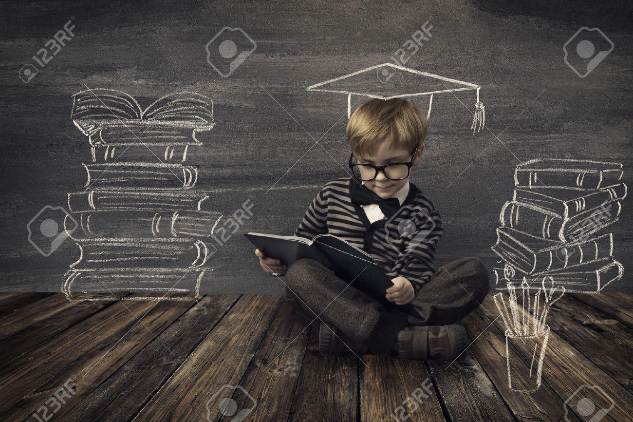 Child Little Boy in Glasses Reading Book over School Black Board with Chalk Drawing, Kids Preschool Development, Children Education Concept - 39762638