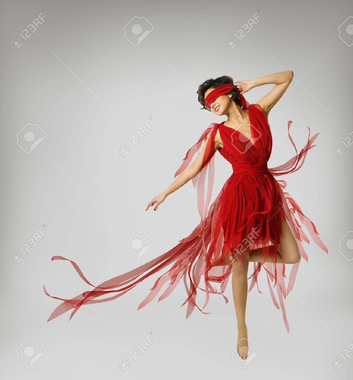 f2b4780bb840 Stock Photo - Woman Artist Dancing in Red Dress, Girl with Band on Eyes,  Model with Ribbon Bandage over light gray background