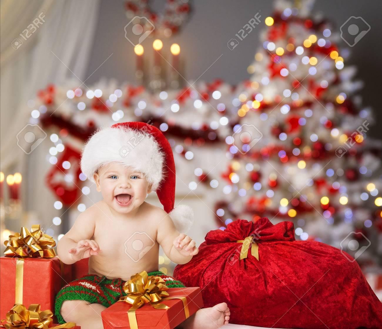 Christmas Baby in Santa Hat, Kid Boy with Xmas Present Gift Box and Bag - 65114199