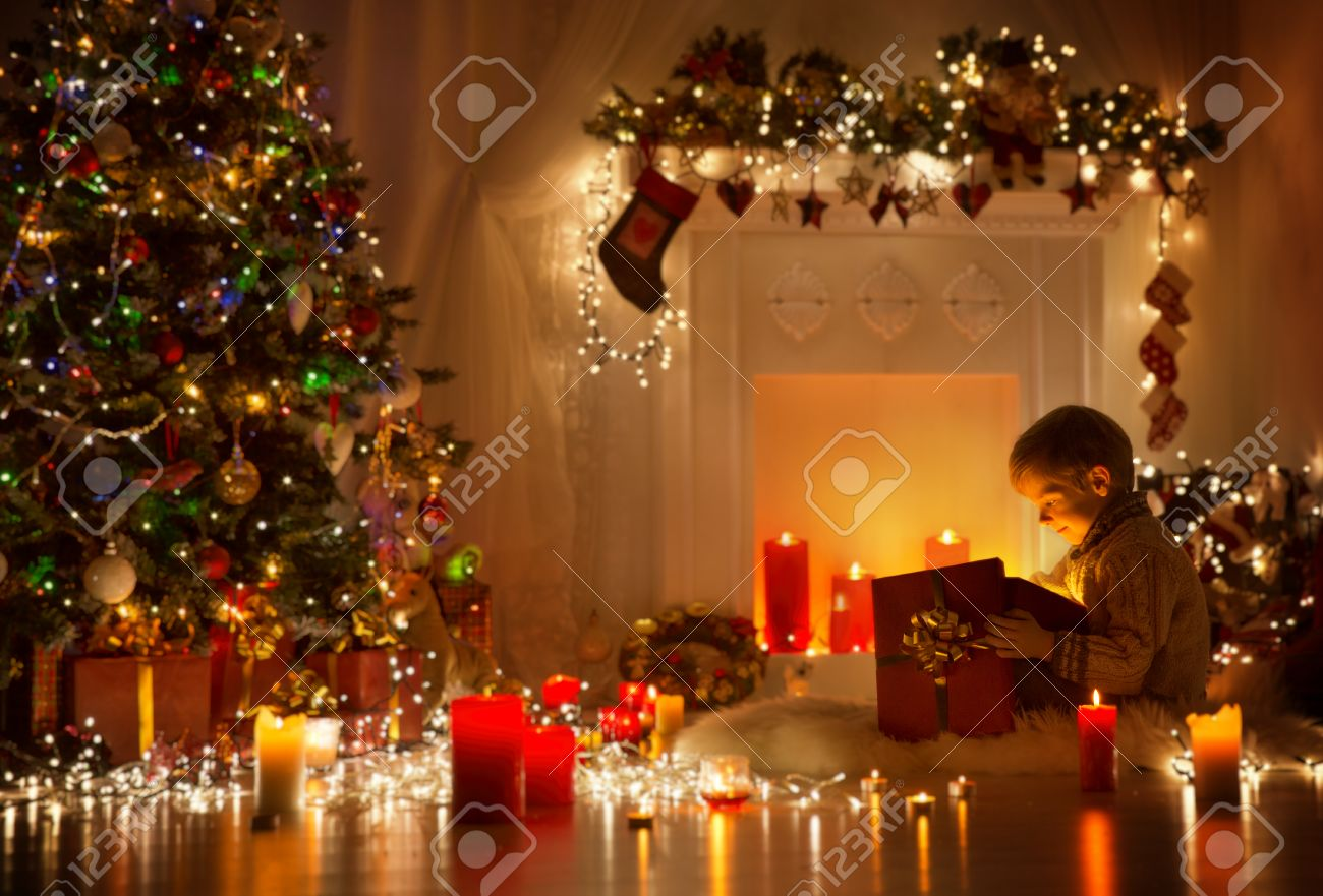 child opening christmas present kid looking to light gift box