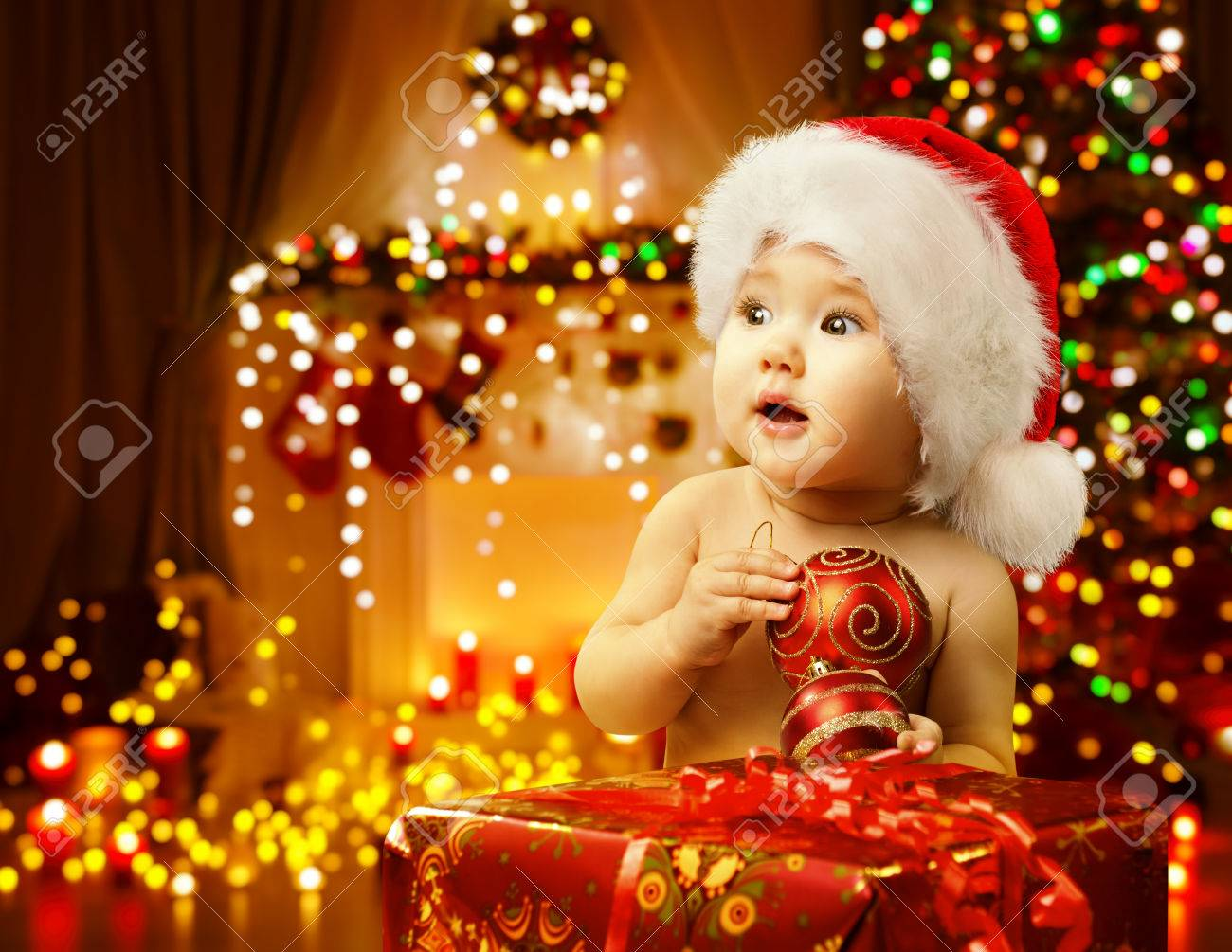 Christmas Baby Opening Present, Happy Kid in Santa Hat, Xmas Gift Box, Child Looking Side - 63802539