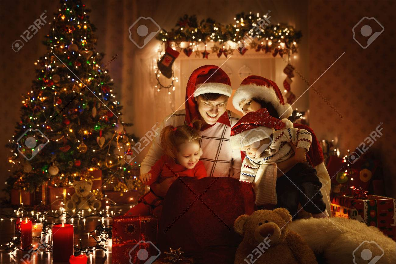 Christmas Family Open Present Gift Bag, Looking to Magic Light in Xmas Interior Stock Photo - 63802540