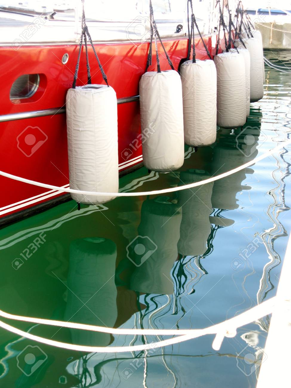 A red sailing yacht with fenders in a marina Stock Photo - 19220650