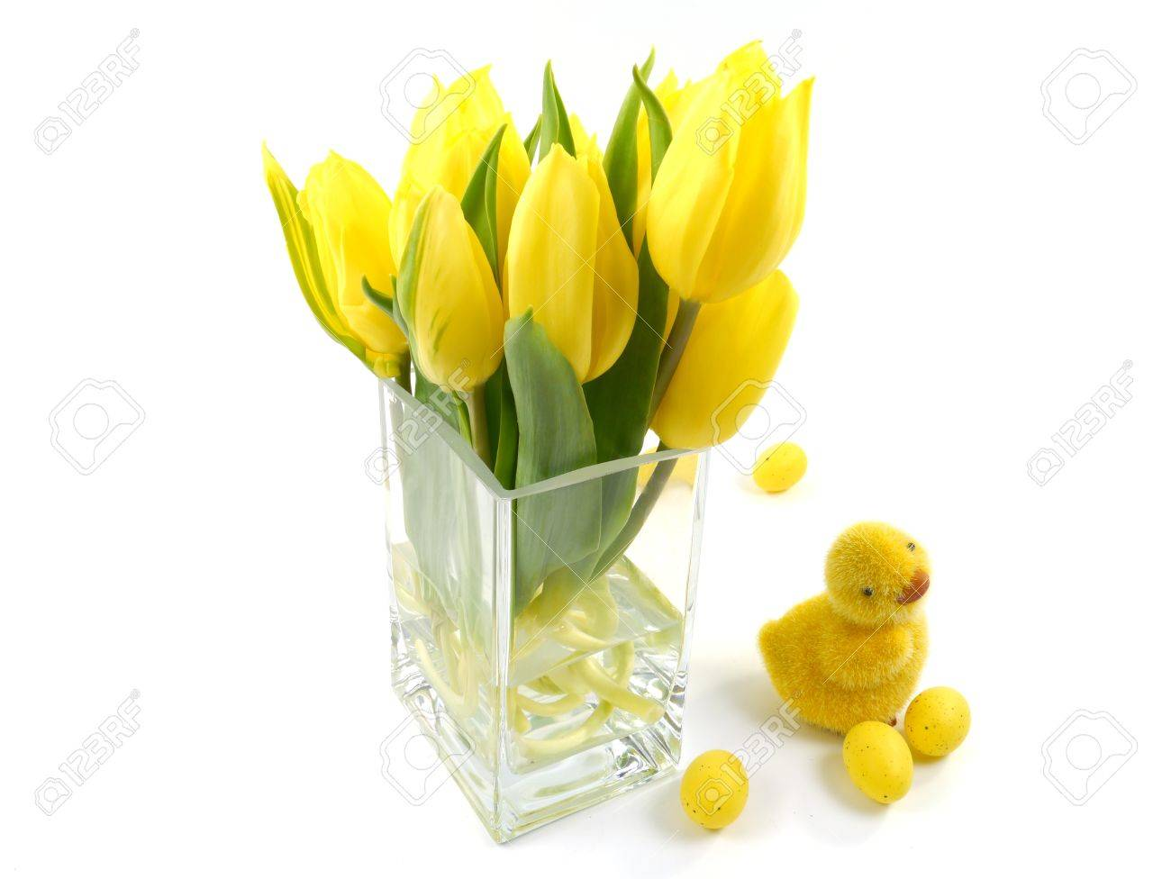 Yellow spring tulips in a vase of glass with an easter decoration yellow spring tulips in a vase of glass with an easter decoration over white stock photo floridaeventfo Gallery