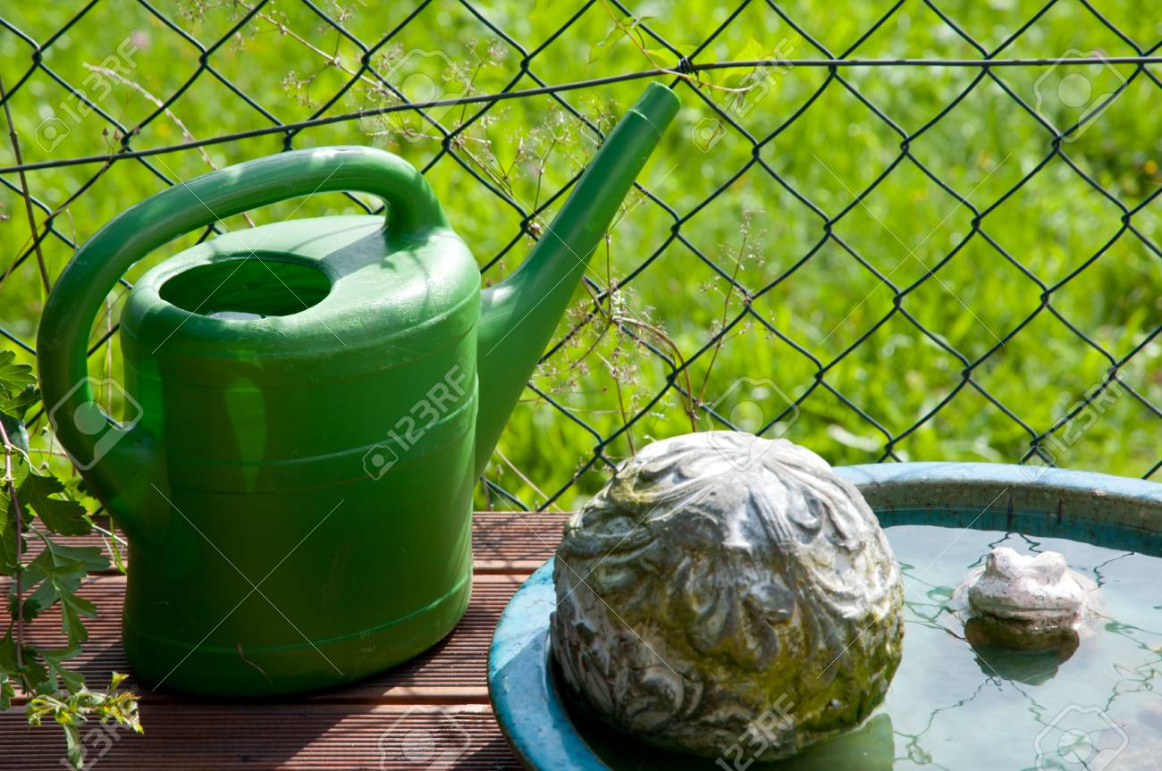Green Watering Can And Bird Bath In Garden Stock Photo   37883034