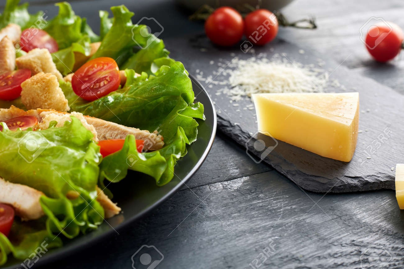 Delicious Caesar salad with cherry tomatoes and croutons and piece and grated parmesan cheese on black serving board. - 154817562