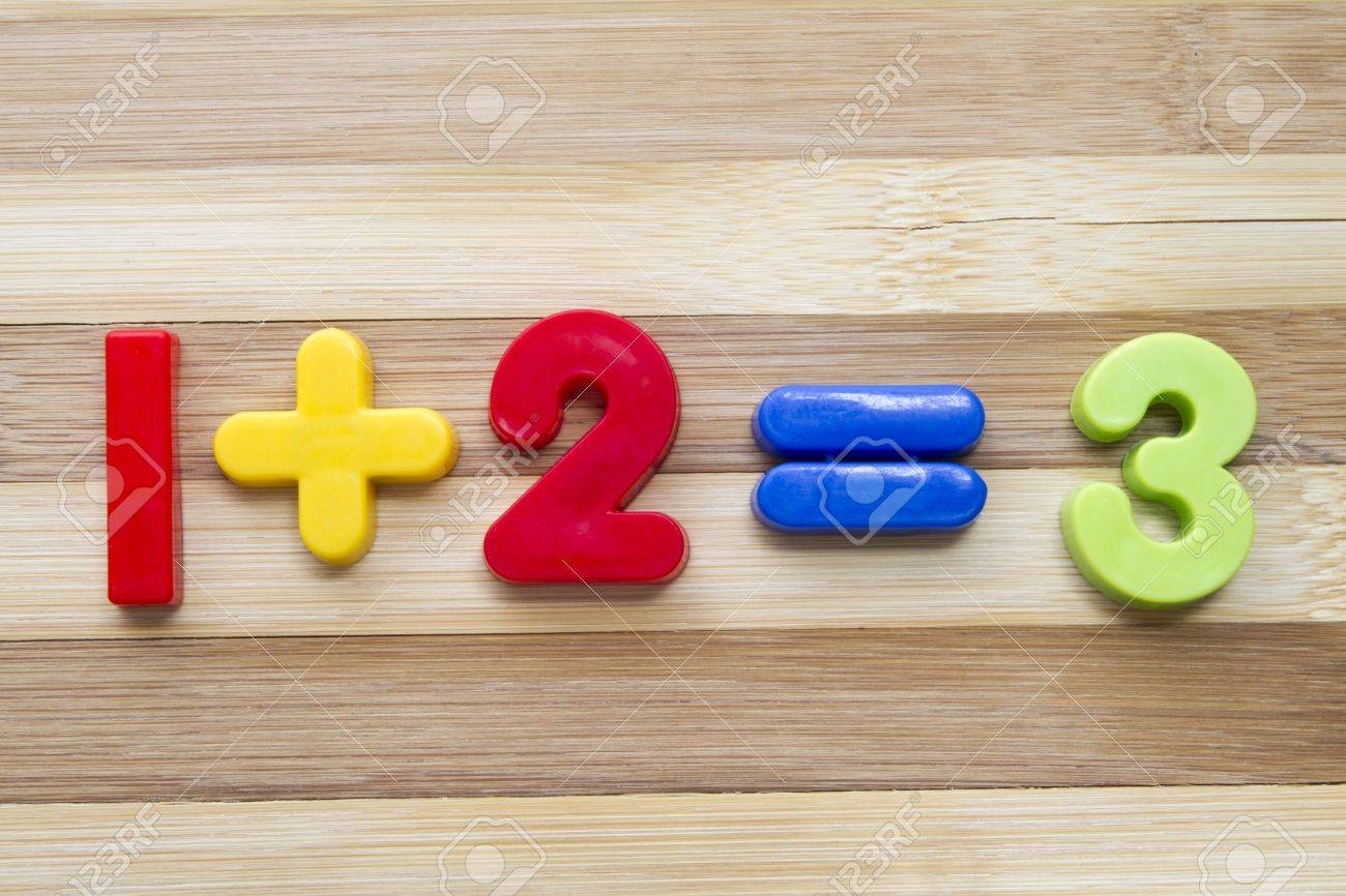 Math example with numbers magnets on wood background Stock Photo - 12962448