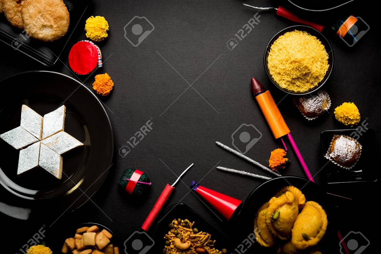 Diwali sweets and snacks arranged in a group with Diya or oil lamp, flowers and Fire Crackers or Patakhe over moody background - 109268744