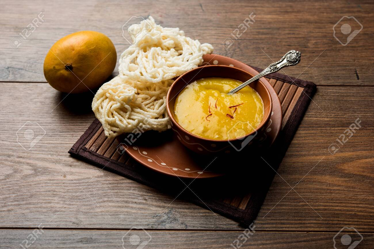 Aam Ras or Alphonso mango pulp with kurdai which is a fried dish made using wheat/gehu. selective focus - 121885516