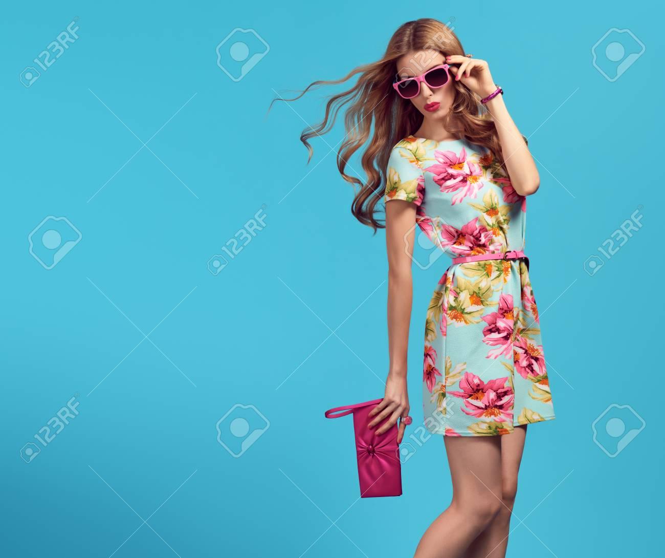 12d7d61e758 Foto de archivo - Moda. Mujer rubia en pose de moda. Señora joven belleza  en vestido de flores Soplando los labios. Moda moda peinado