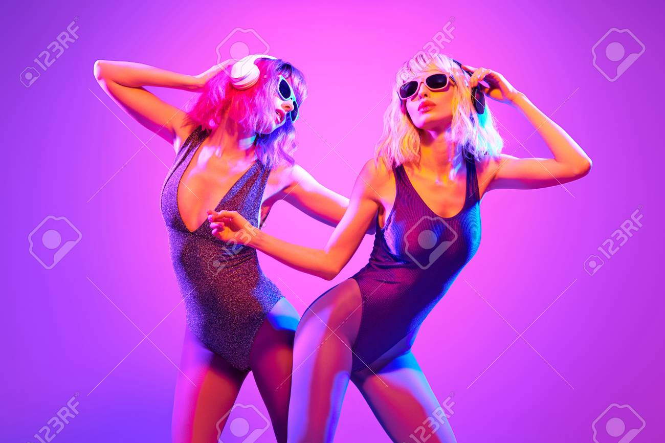 Two sexy fashionable DJ girl in party outfit dance  Colorful