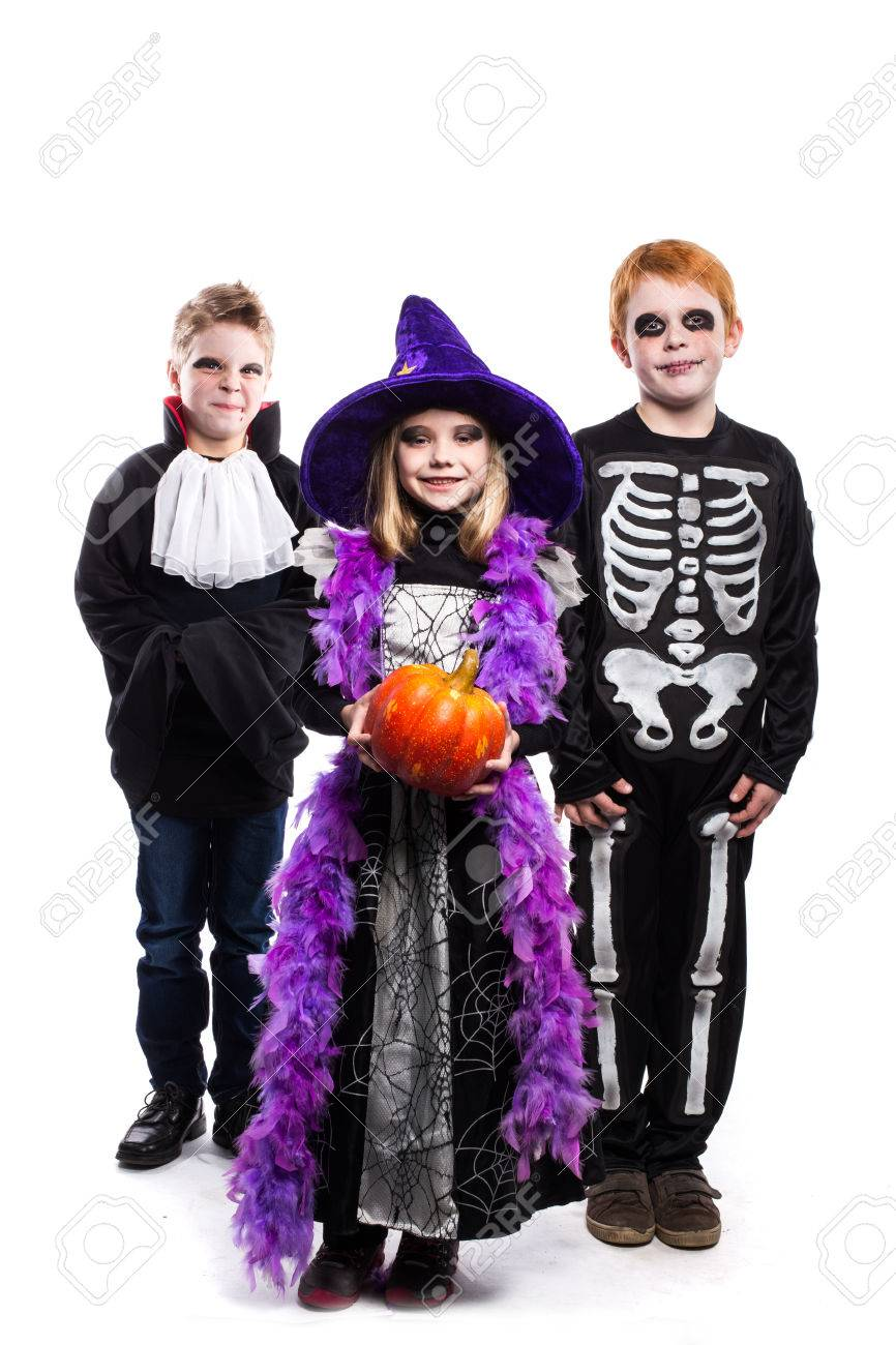 one little girl and two boys dressed the halloween costumes witch skeleton vampire