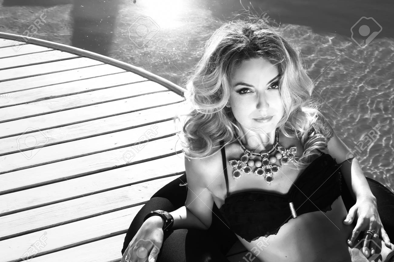 Black and white photo of beautiful sexy blonde woman laying near the swimming pool in black
