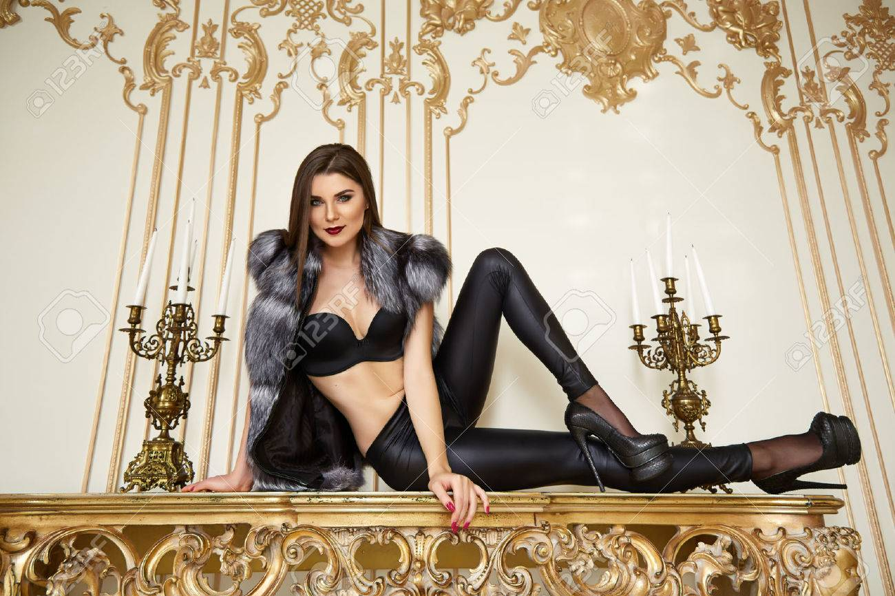 Beautiful young brunette woman with long hair thin slender figure perfect body and pretty face make-up wearing leather djeans fur bra high heels gold interior luxury furniture party - 47499128