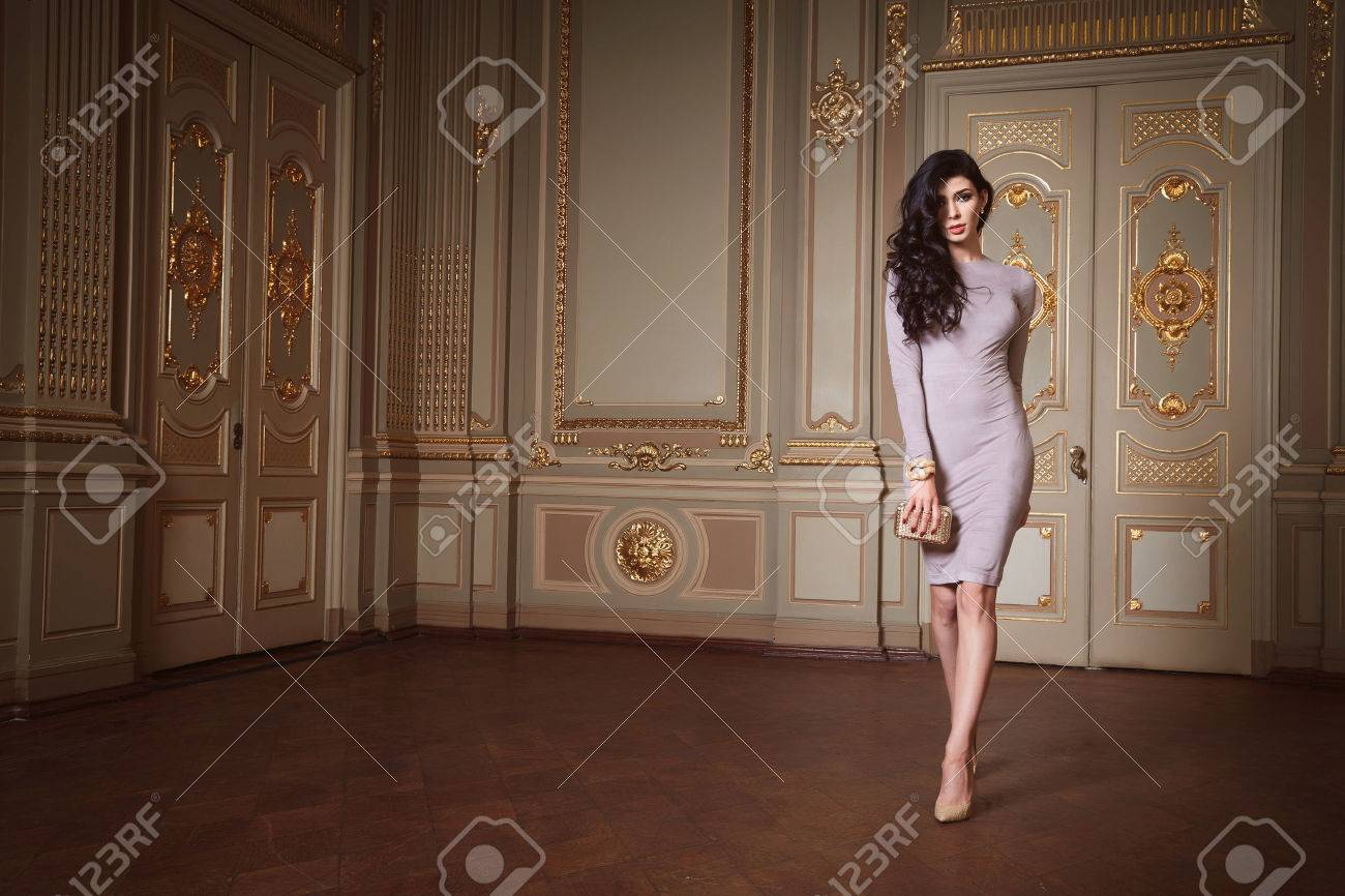 Beautiful woman in elegant dress fashionable autumn Collection of spring long brunette hair makeup tanned slim body figure accessories interior luxury castle gold monogram baroque palace of Queen - 48834918