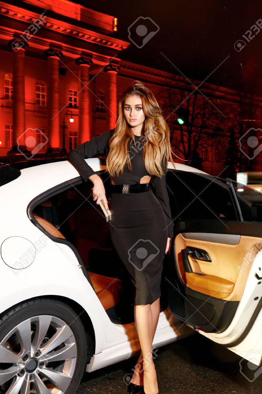 Beautiful young blonde wearing evening makeup in elegant fitting dress fashionable stylish sitting in cabin of expensive car comes out of it in hand handbag luxury rich life going party concert - 51002483