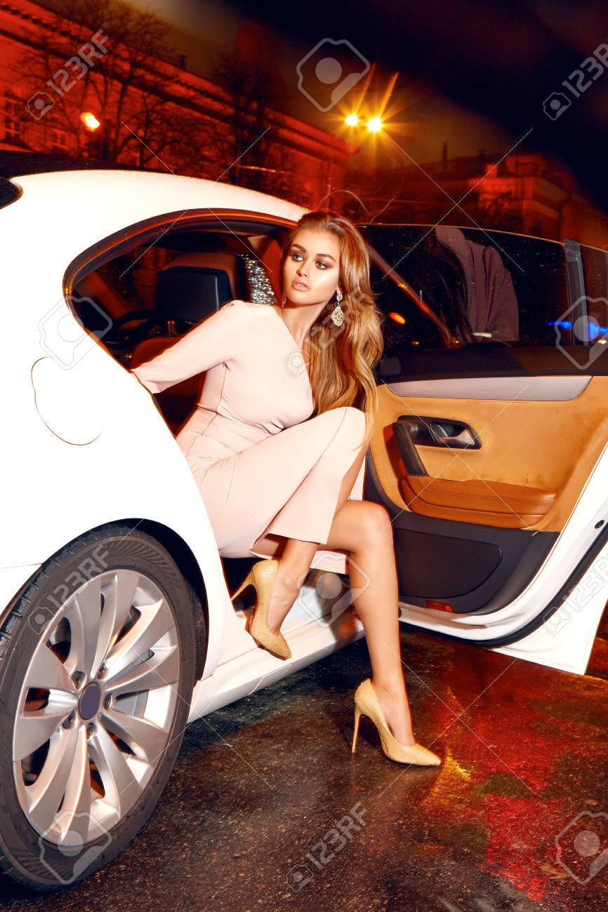 Beautiful young blonde wearing evening makeup in elegant fitting dress fashionable stylish sitting in cabin of expensive car comes out of it in hand handbag luxury rich life going party concert - 51002569