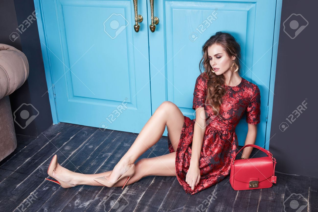 Beautiful young woman in smart evening dress red silk dress new stylish fashion collection autumn winter season, long brown hair, shoes, interior blue door in the bedroom room. - 52797805