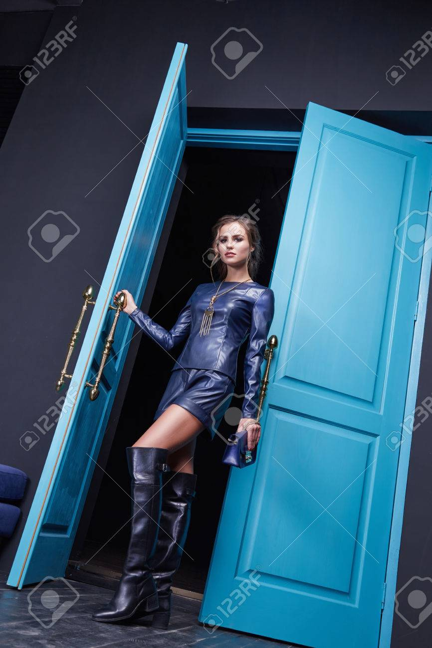Sexy beautiful woman wear blue leather costume fashion style clothes accessory bag cosmetic make up blue door interior wear collection. - 52797888