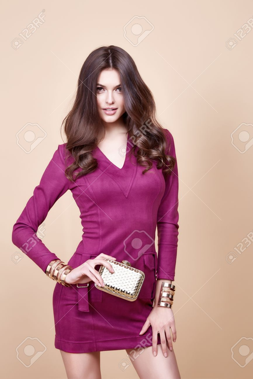 Glamour beautiful brunette women, looks like a model, wearing evening make up in short red dress with small yellow bag in hands in fashion pose with amazing figure, perfect shape girl hairdo. - 54632889