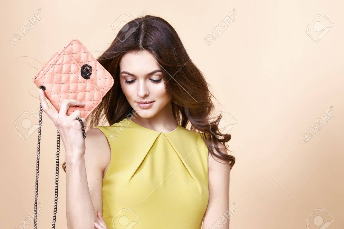 Glamour fashion woman long brunette curly hair natural evening makeup wear short stylish yellow cotton dress from new catalog spring summer collection accessory handbag jewelry body shape care. - 54633051