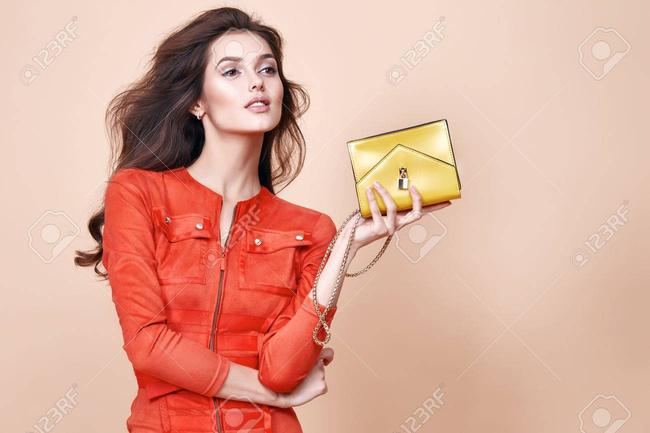 Sexy glamour beautiful woman wear short fashion style dress party style clothes for date hold small gold clutch bag perfect body shape tan skin dance natural evening make up long dark curly hair. - 54633078