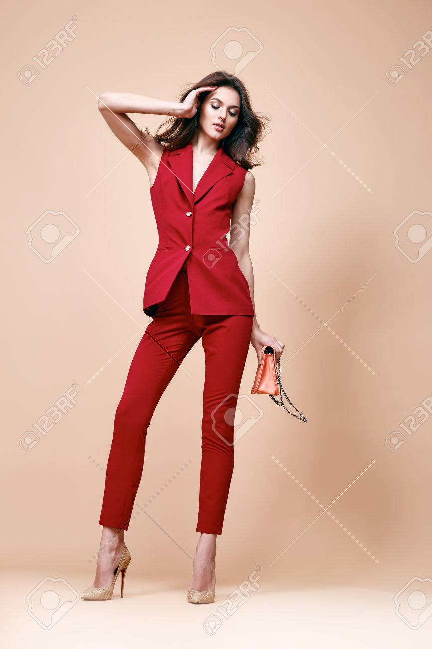 Beautiful brunette woman wear red silk costume jacket and pants summer collection clothes for business lady casual work office style hold small lather goods bag make a pose fashion model catalog. - 54633098