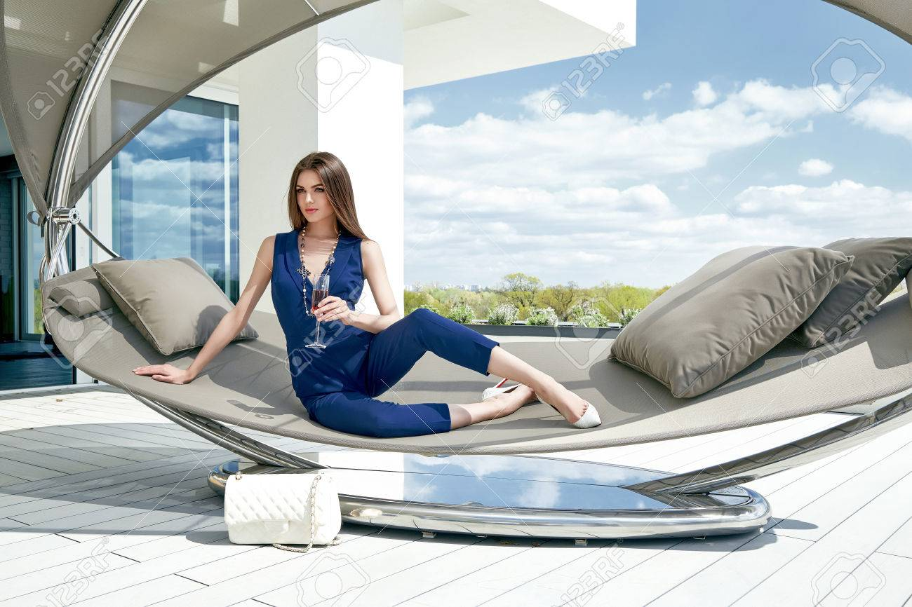 Brunette woman glamour fashion luxury life style lady sit on stylish hammock modern interior building house party time drink champagne accessory lather bag summer blue sky nature resort success. - 57568074