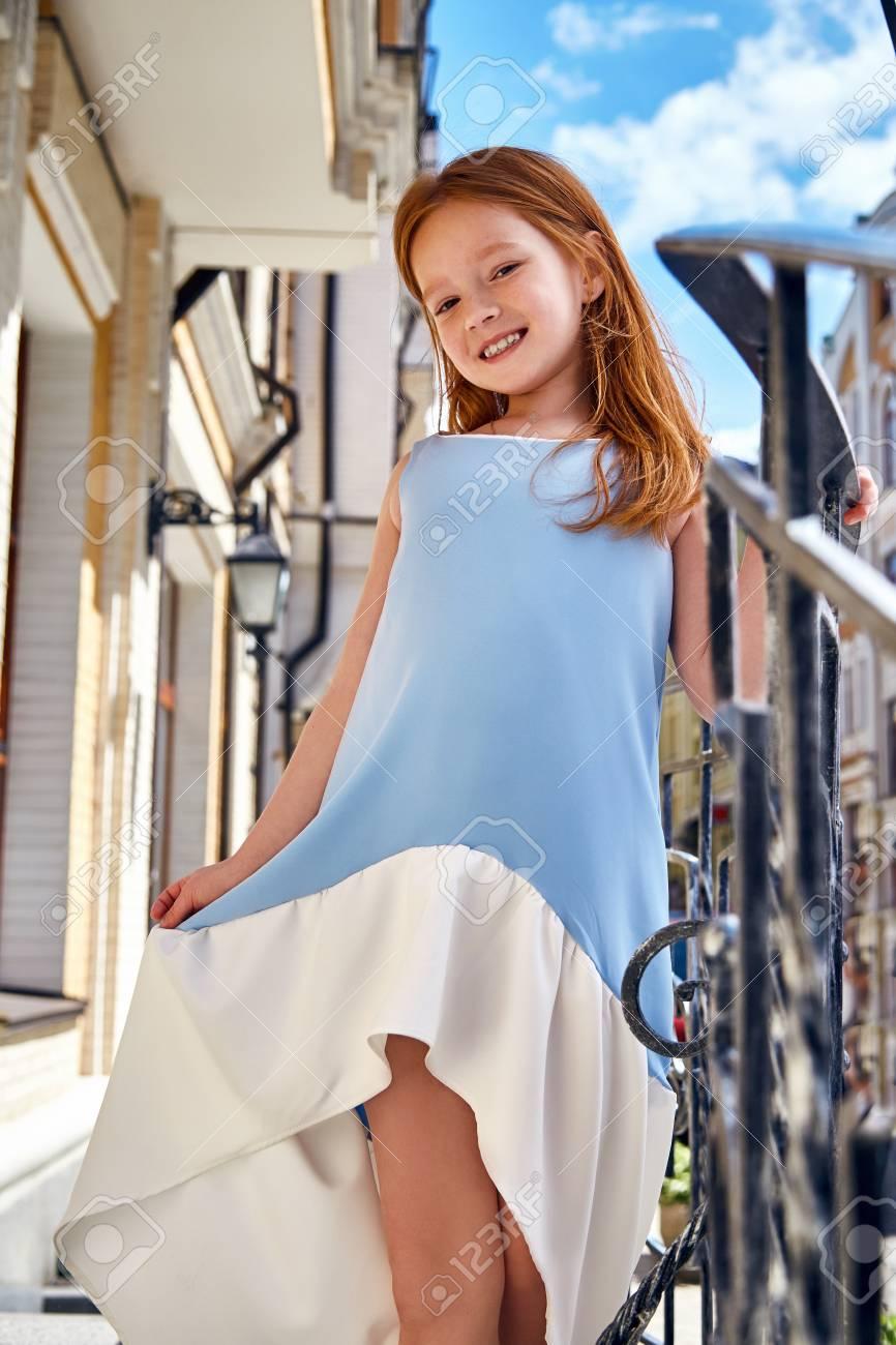Niño Chico Joven Y La Belleza De La Hija Felices Jugar Bastante Divertido  Bebé Cara Pequeña Ropa De Moda De Pie Vestido Azul Niña En La Ciudad De Sol  ... bdd7e7906d9