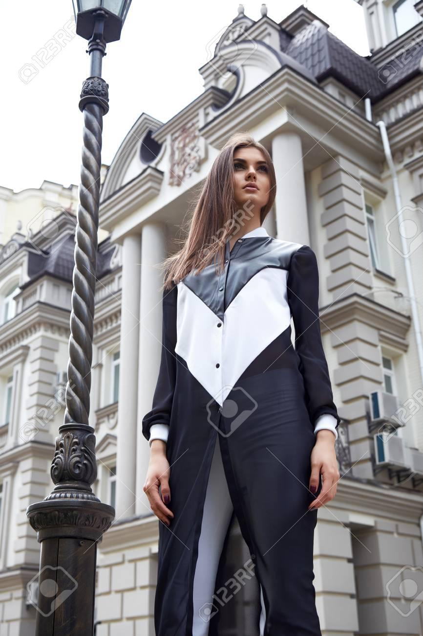 486d02890dd2 Bella donna che cammina sulla strada tra moderni edifici della città e  aprendo la calda signora clima estivo indossa un elegante abito bianco e  nero flirt ...