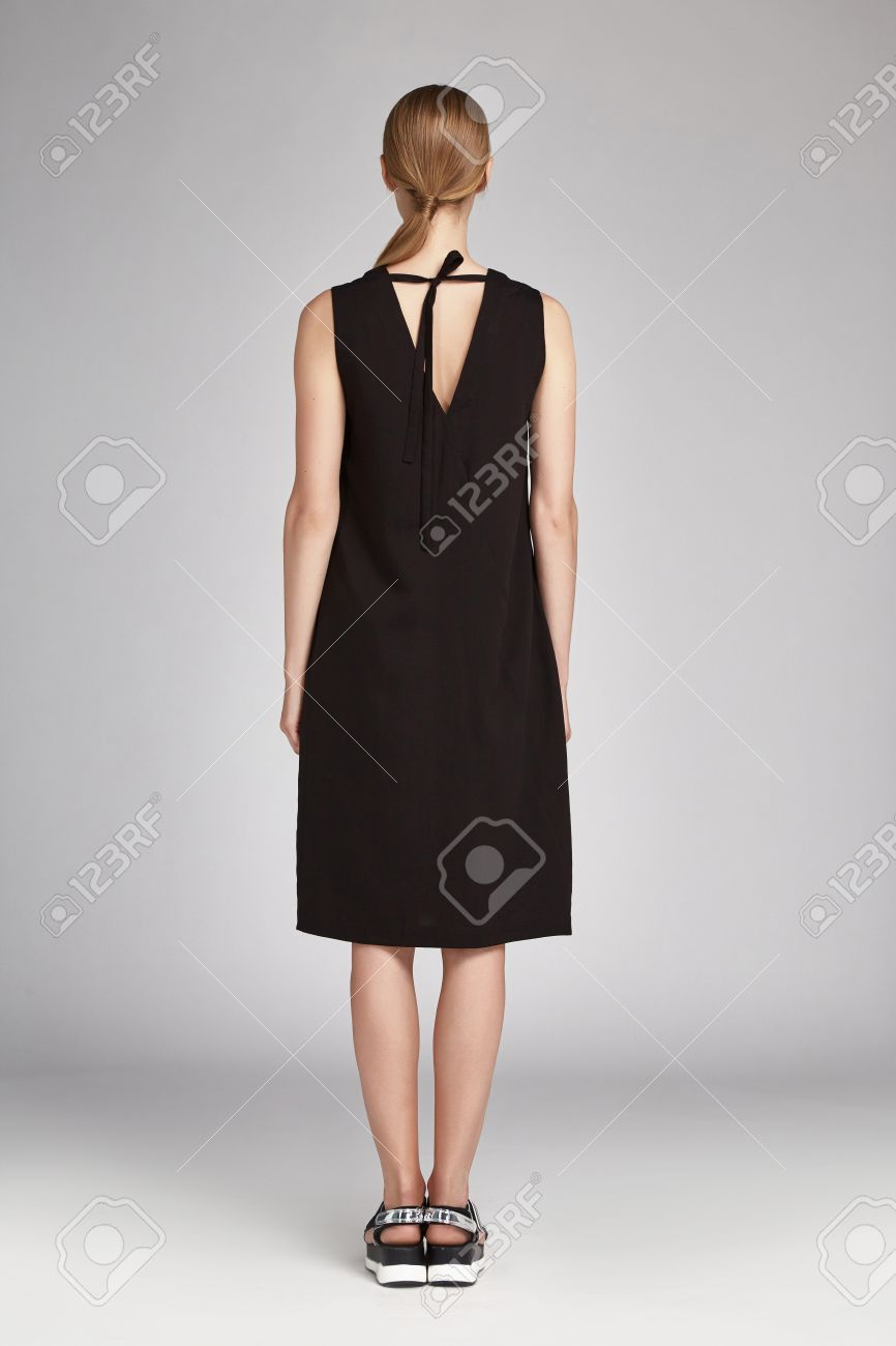 美しいセクシーな女性金髪長い髪黒いシルクのドレス靴を着用、オフィス、カジュアルな会議カタログ冬コレクション毎日通り灰色の背景のビジネス  スタイルのモデルの服のファッション