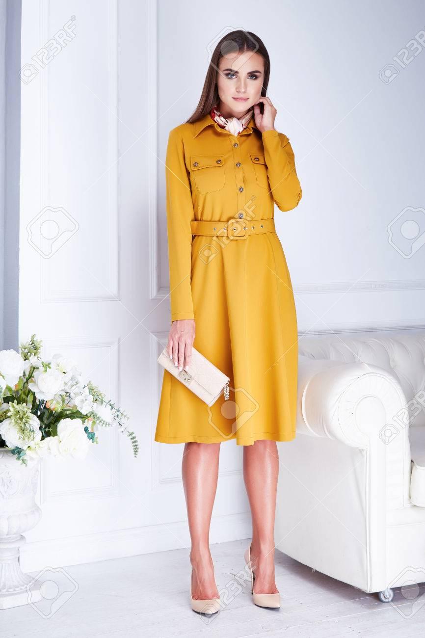 b3907d475 Hermosa Mujer Morena Sexy Desgaste Elegante Vestido De Color Amarillo  Llevar A Cabo Pequeños Bolsos De Tacones Altos Ropa Para La Reunión De La  Fecha ...