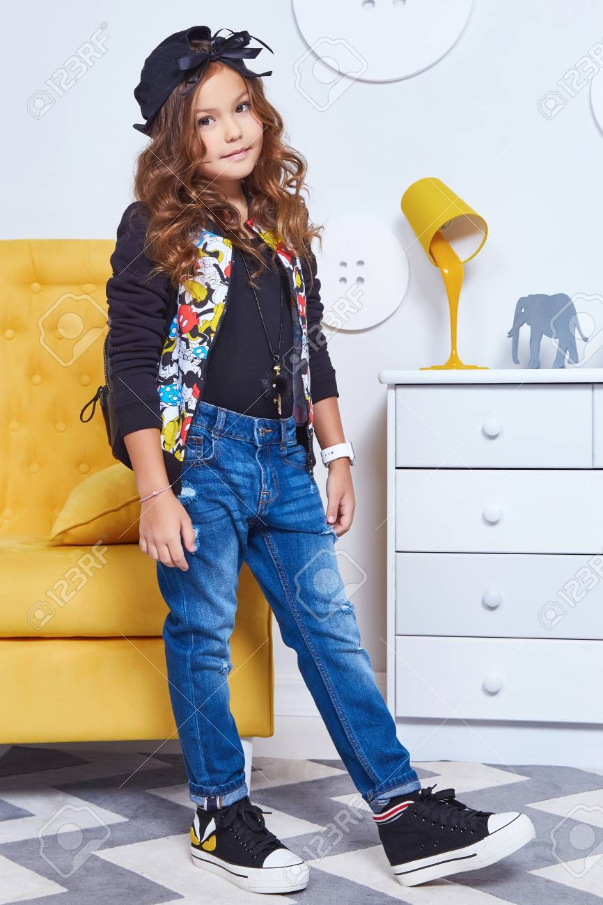 97f76b231 Beautiful cute pretty little girl baby blond curly hair fun to play in the  children room on the big yellow chair dressed in denim jeans trousers vest  style ...