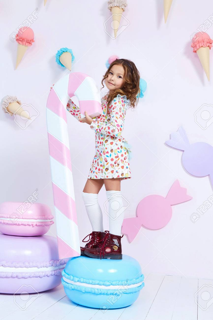 Cute little baby girl fashion pretty model dark blonde curly lady hair funny child birthday party fun children room candy bar sweet ice cream play with toy wear style clothes dress shoes decoration. - 71711767