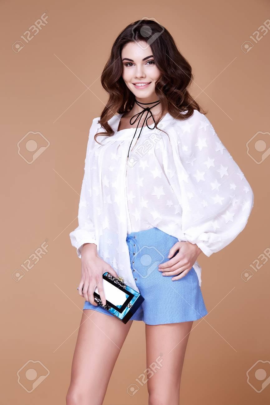 5696d092e7d0 Sexy brunette woman wear short blue cotton short and silk summer collection  blouse perfect body shape