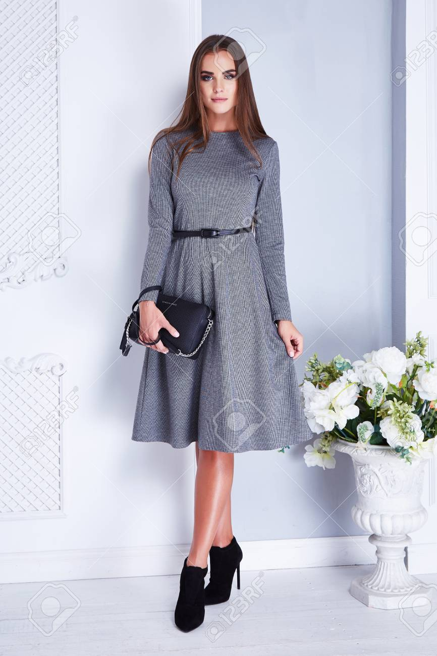 2079850fef5 Beautiful sexy brunette woman wear elegant fashion silk dress hold small  bag high heels clothes for date meeting summer collection model in white  room ...
