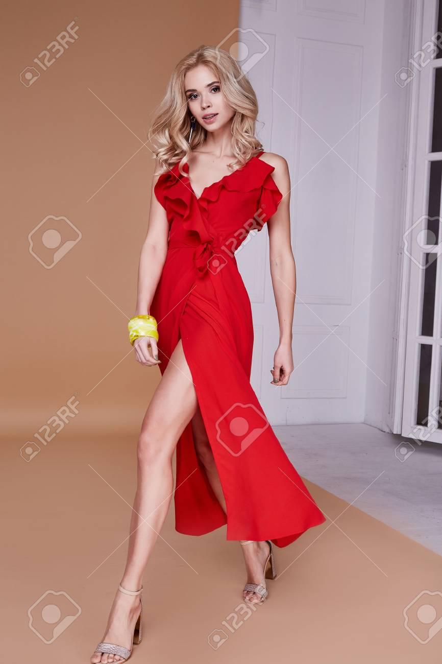 e279310e5b0e Beautiful sexy young business woman blond hair with evening makeup wearing  long red silk dress high