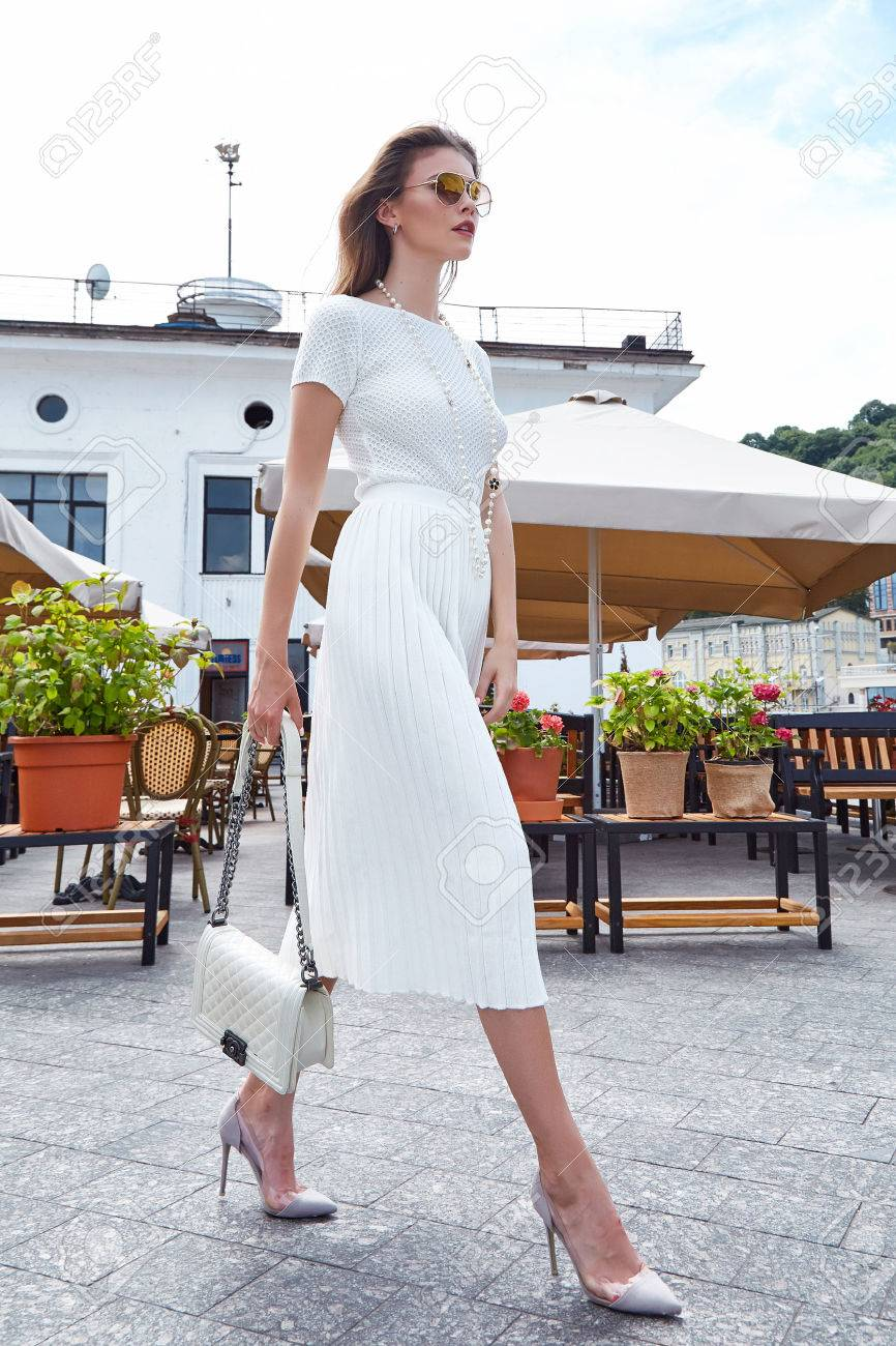 Brunette woman fashion style street look elegant walk cafe restaurant date meeting businesswoman success wear white dress accessory bag sunglasses high-heels shoes clothes summer collection. - 84650789