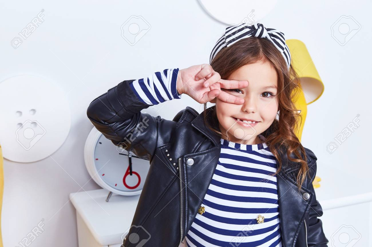 Portrait of small little lady pretty girl cute kid smile hand curly  brunette hair wear fashion style clothes for baby strip t-shirt lather  jacket hat bow ...